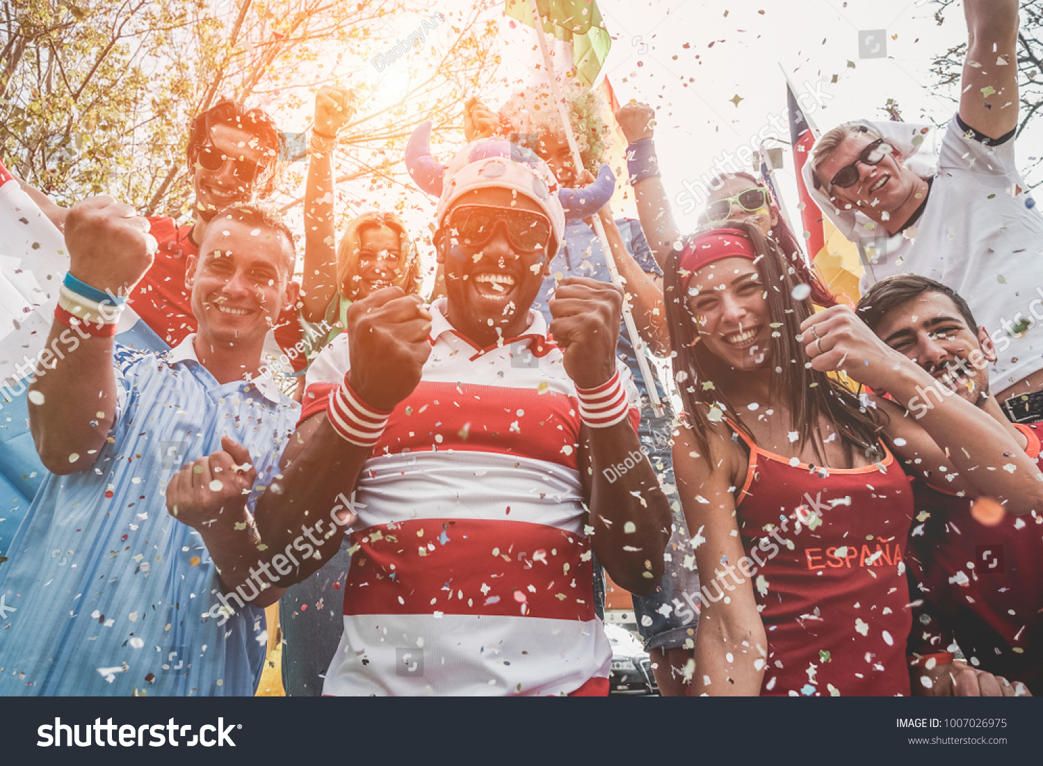 Multinational football supporters celebrating the begin of world competition - Happy multiracial people having fun together outside of stadium - Main focus on black man - Sport and bonding concept