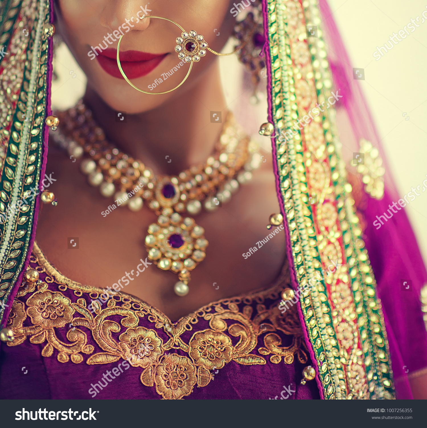 Portrait of beautiful indian girl. Young hindu woman model with kundan jewelry set. Traditional India costume lehenga choli or sari #1007256355