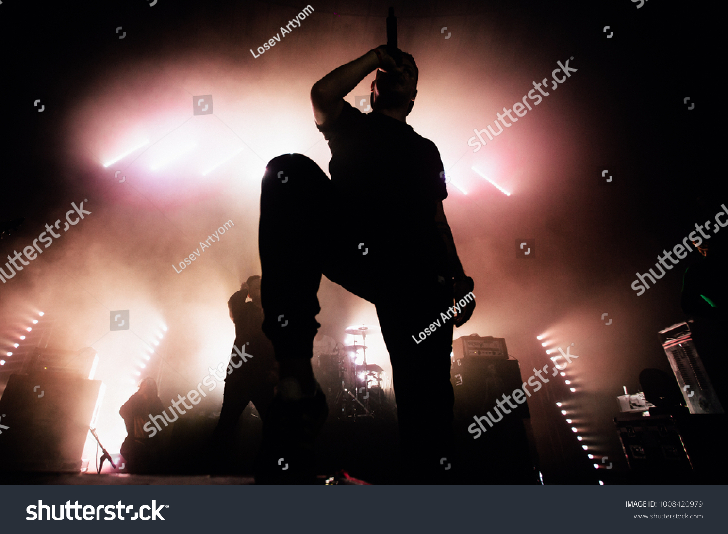 A dark silhouette of a singer on the stage. Good-looking background, bright stag lights. A concert of a famous music band #1008420979