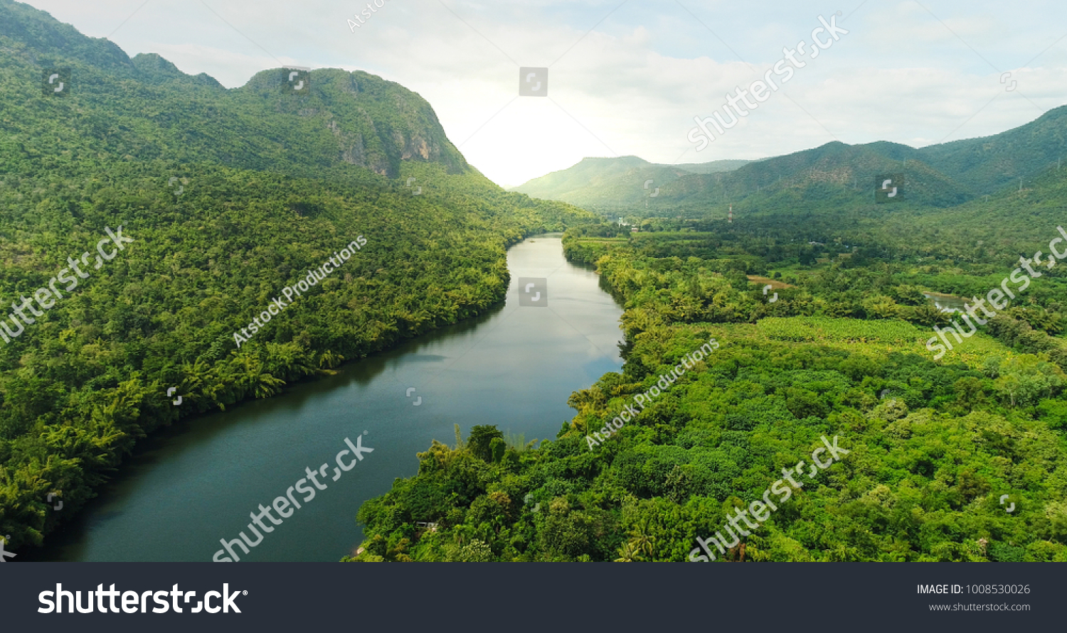 Beautiful natural scenery of river in southeast Asia tropical green forest  with mountains in background, aerial view drone shot #1008530026