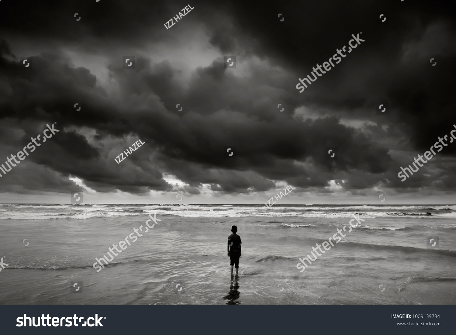 Alone boy near the beach with dramatic stormy sky during monsoon season