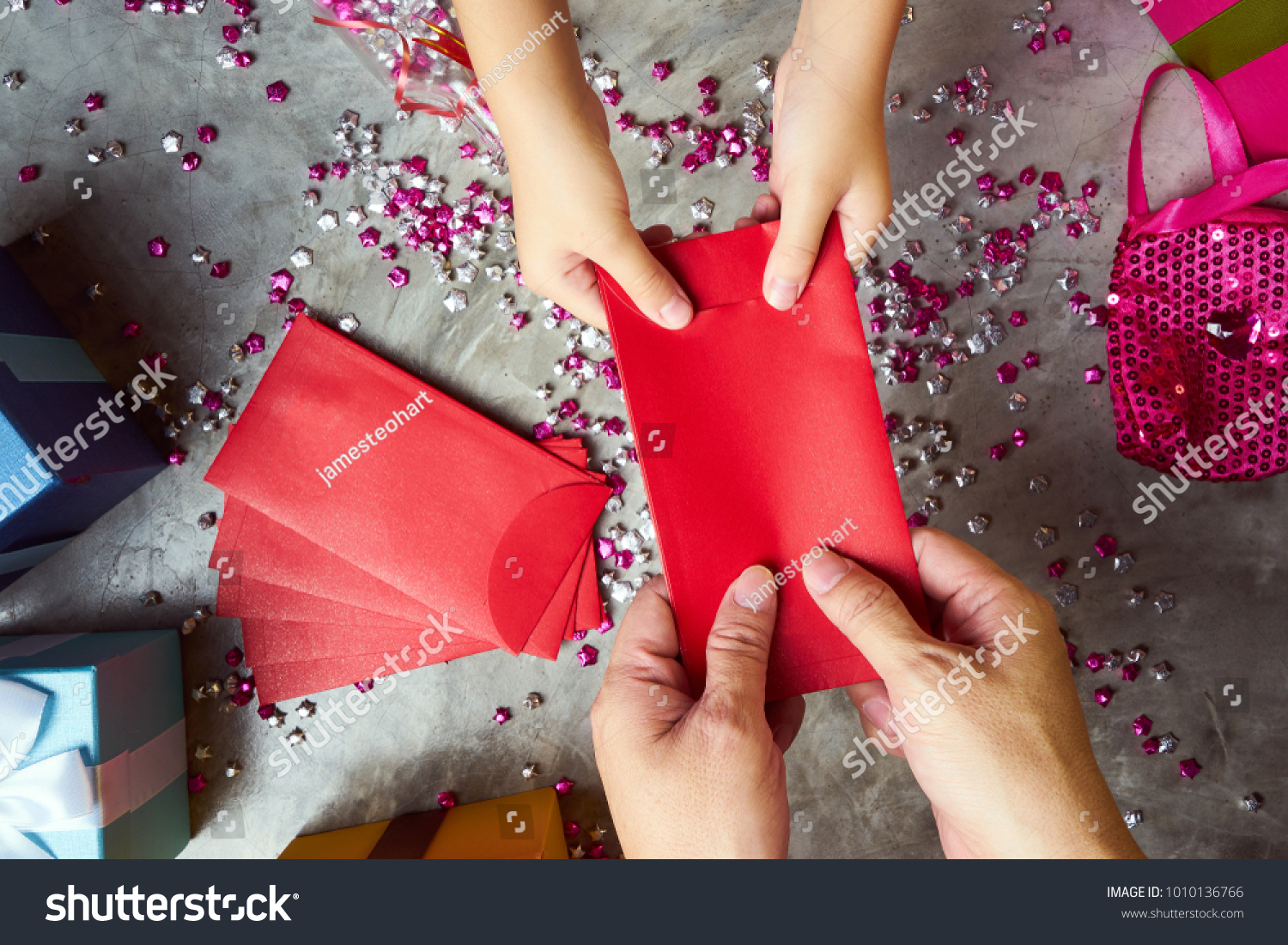 Close up hands of parent giving a red envelope or money red packet to child  .  Chinese new year and Lunar new year festival concept background . Top view . #1010136766