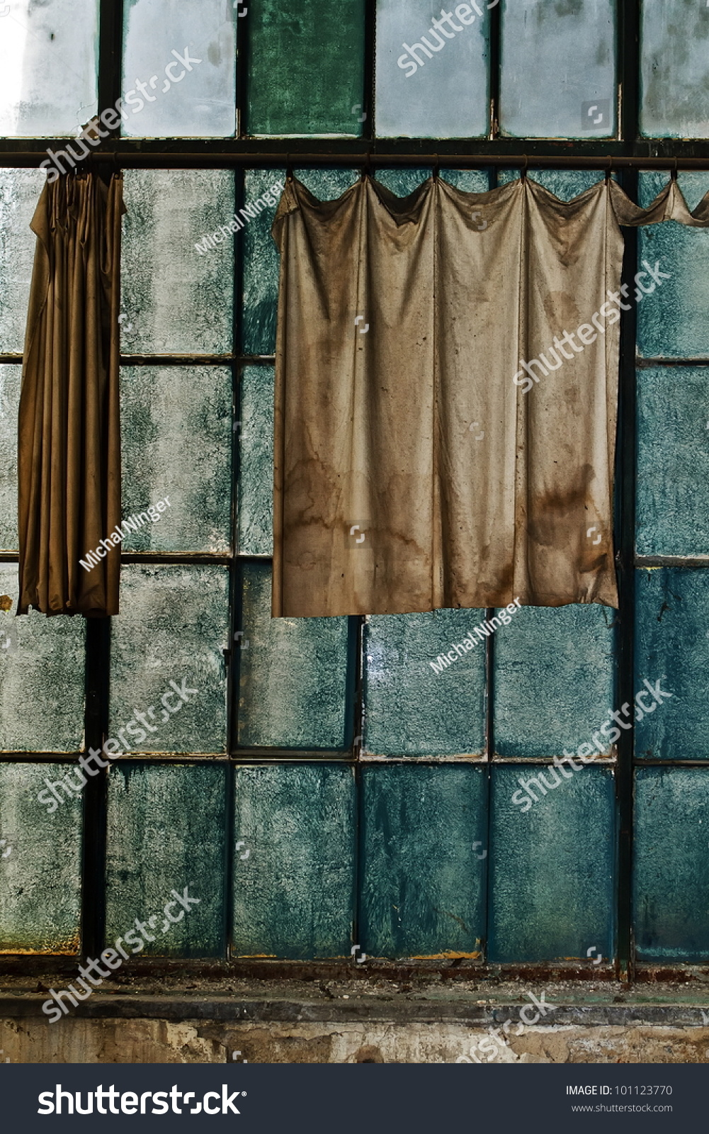 dirty curtains in the windows at a workshop hall