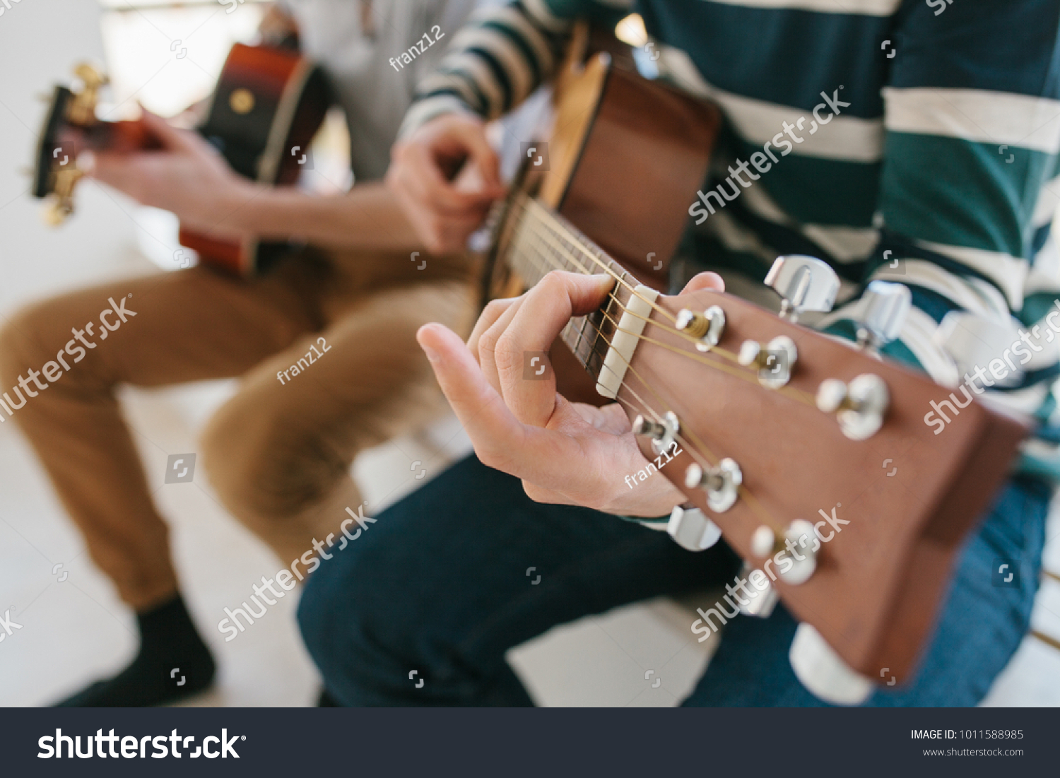 Learning to play the guitar. Music education and extracurricular lessons. Hobbies and enthusiasm for playing guitar and singing songs. #1011588985