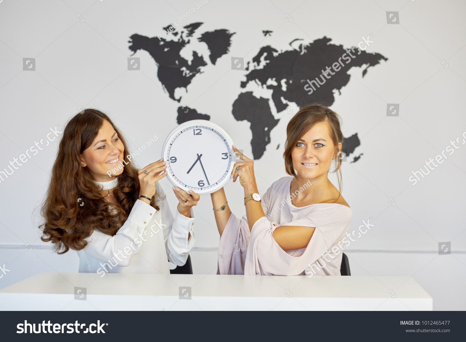 Two smiling women sit desk holding stock photo royalty free two smiling women sit at desk holding wall clock against world map gumiabroncs Image collections