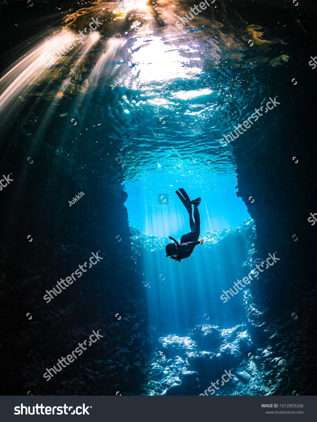 Girl diving in cavern with lightbeams coming on top of her #1012803268