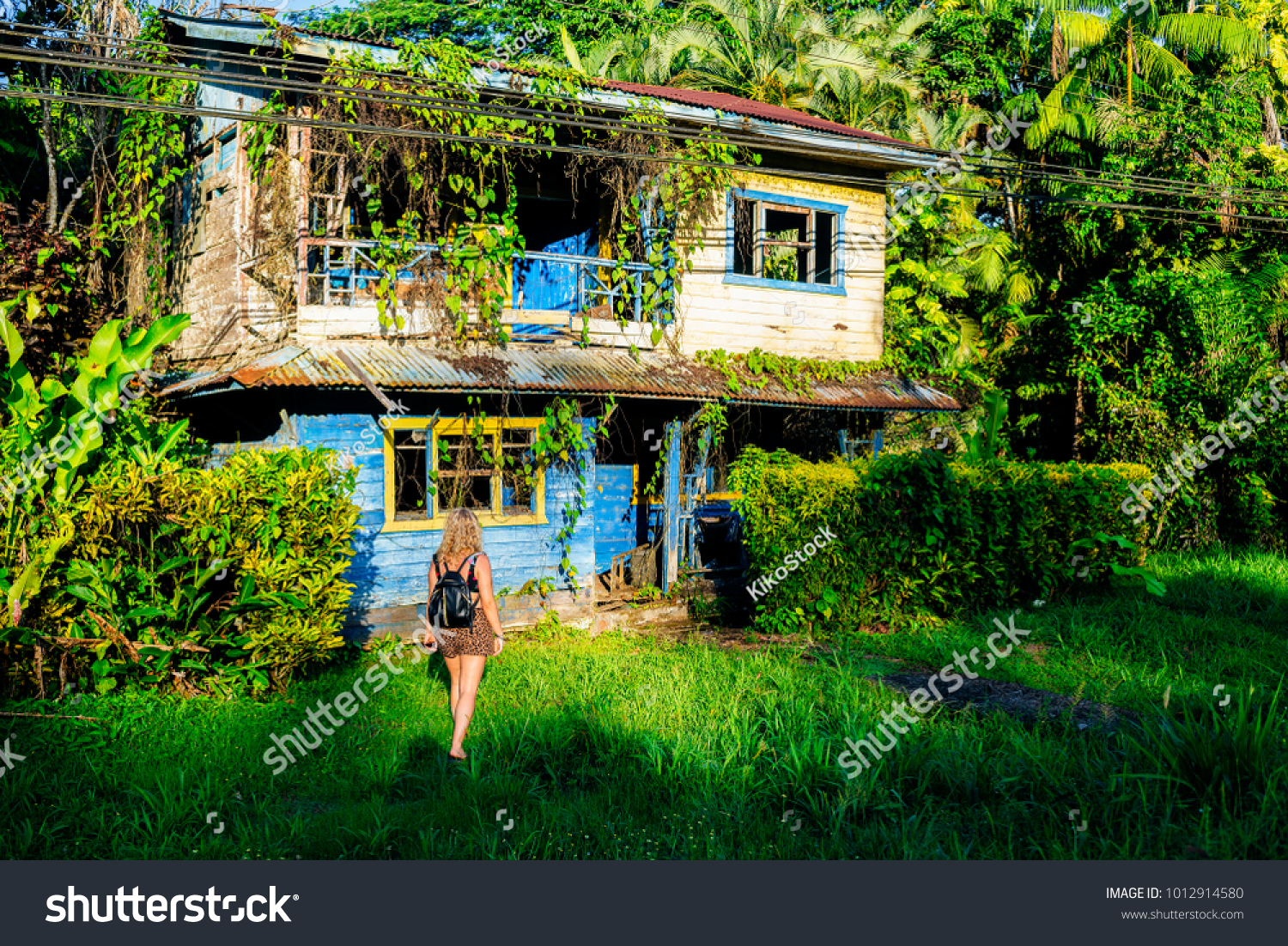 stock-photo-woman-in-front-of-abandoned-house-in-cahuita-puerto-limon-costa-rica-1012914580.jpg