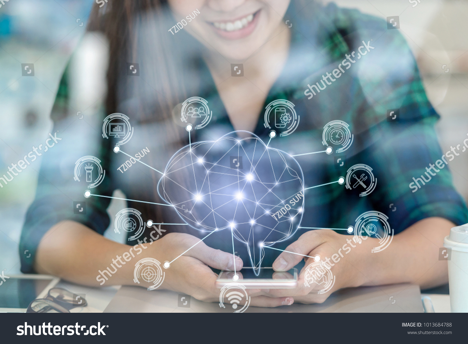 Polygonal brain shape of an artificial intelligence with various icon of smart city Internet of Things Technology over Asian businesswoman hand using the smart mobile phone,AI and business IOT concept #1013684788