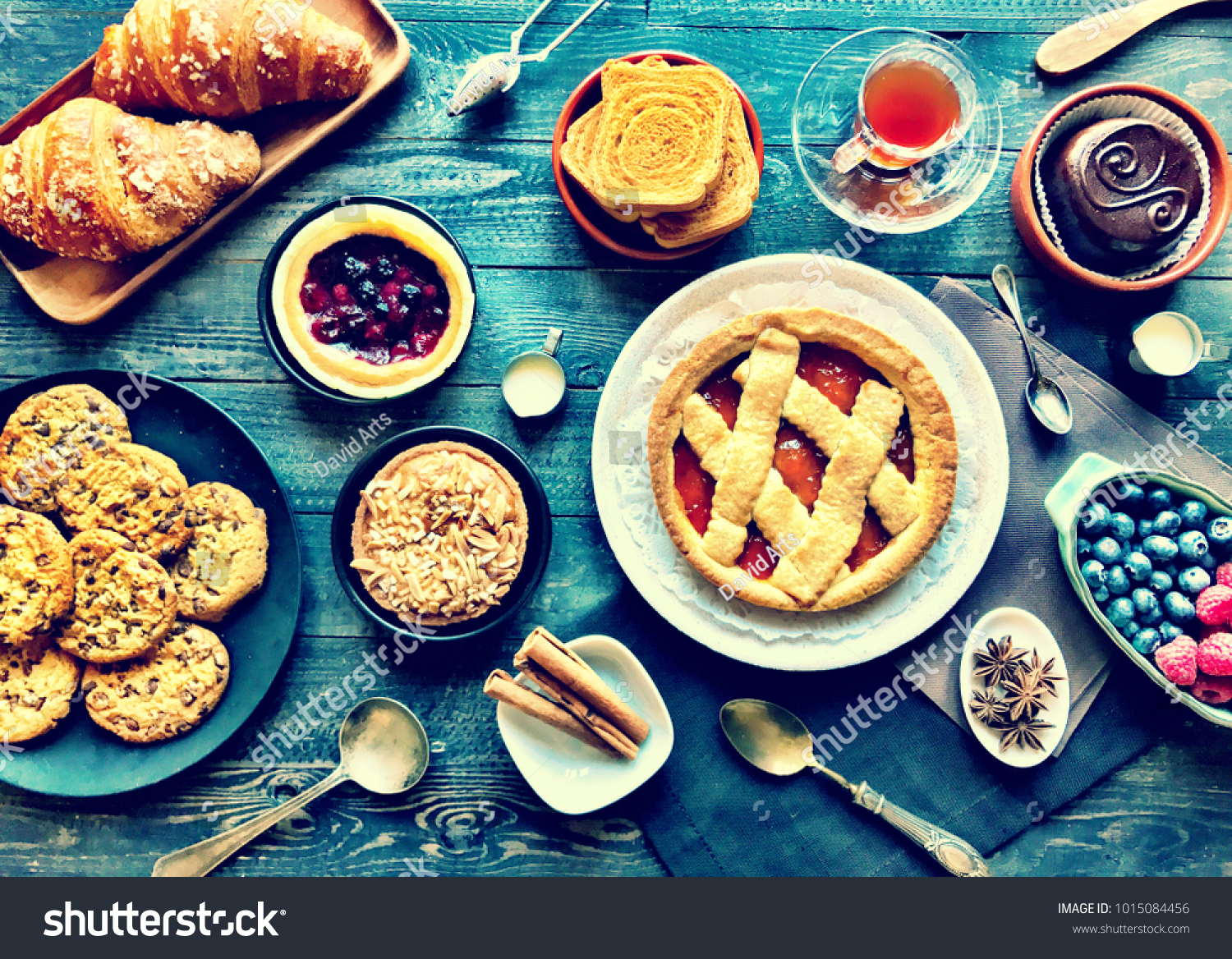 Top view of a wood table full of cakes, spices and more breakfast classic sweet foods. #1015084456