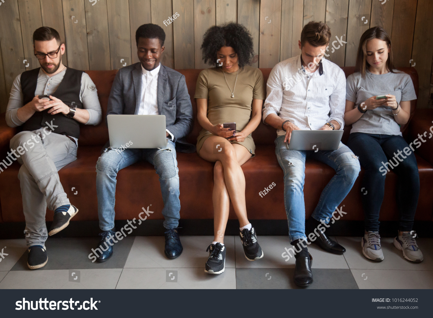 Multicultural young people using laptops and smartphones sitting in row, diverse african and caucasian millennials entertaining online obsessed with modern devices waiting in queue, gadget addiction #1016244052 - 123PhotoFree.com