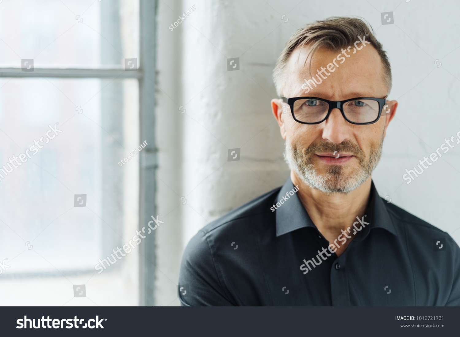 Bearded middle-aged man wearing glasses looking at camera with a serious expression in a close up head and shoulders portrait #1016721721