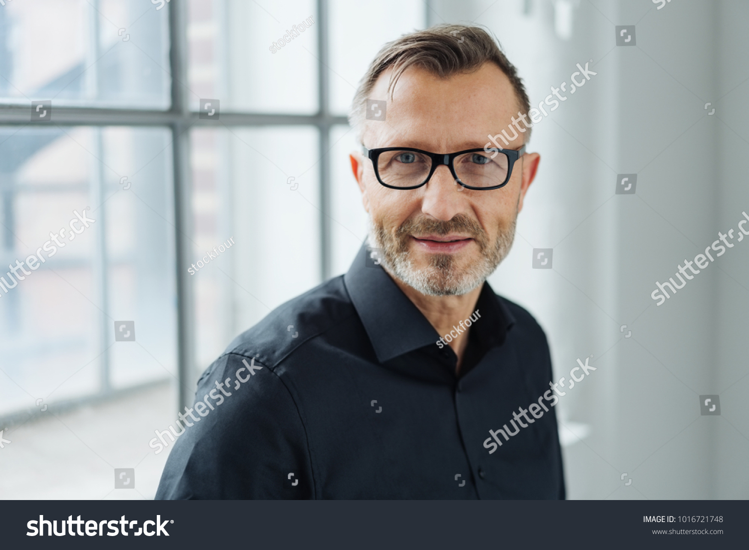 Close-up portrait of a middle-aged man wearing black shirt and eyeglasses while looking at camera with confidence in the office #1016721748