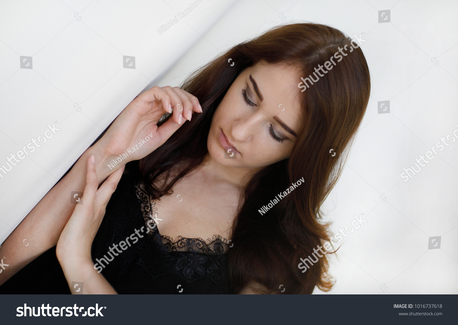 Portrait of a calm and sexy young beautiful woman with flowing dark hair,  dressed in