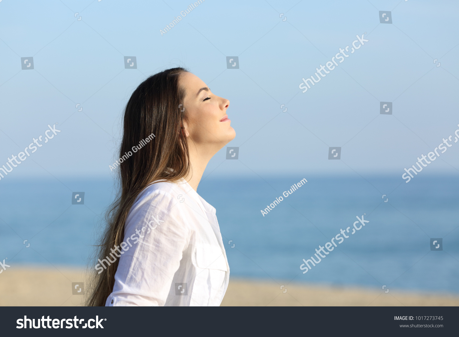 Side view portrait of a woman relaxing breathing fresh air on the beach #1017273745