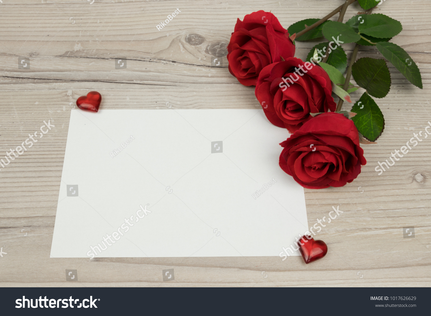 Red roses and a blank invitation card on wooden background ...