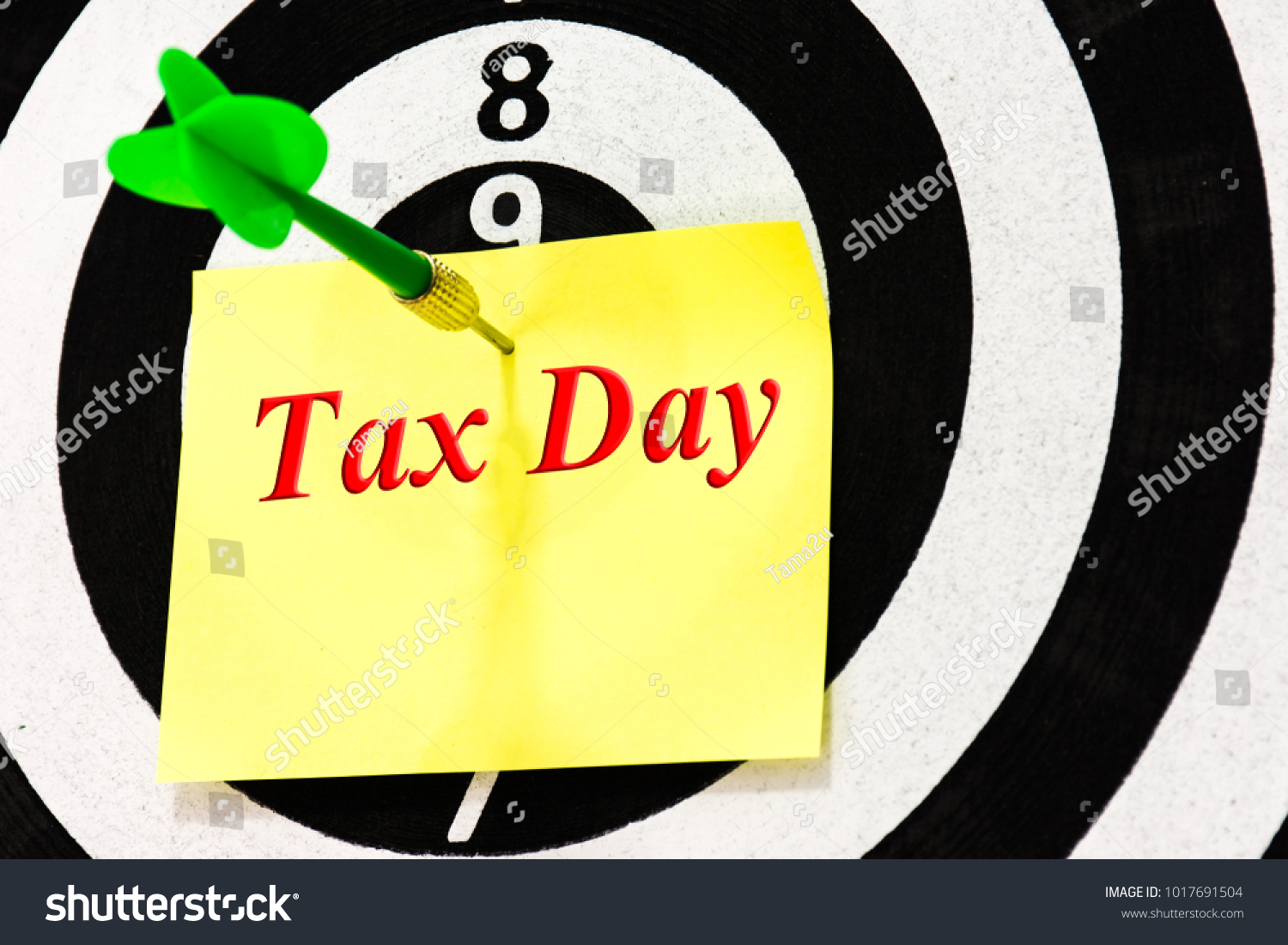 tax day note on dart arrow hitting background dart board game target of tax day