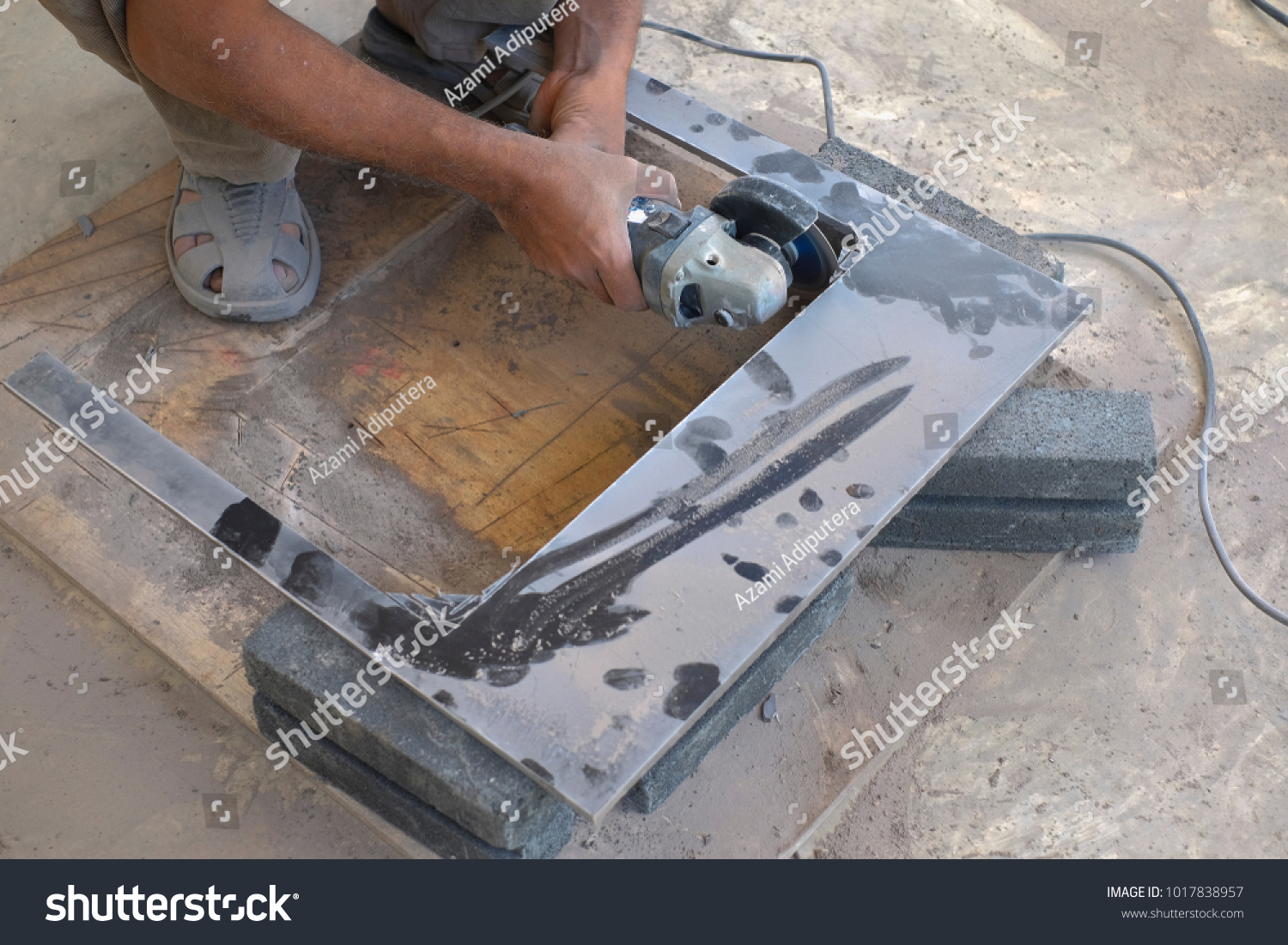 Worker Cutting Floor Tiles With Angle Grinder At Construction Site