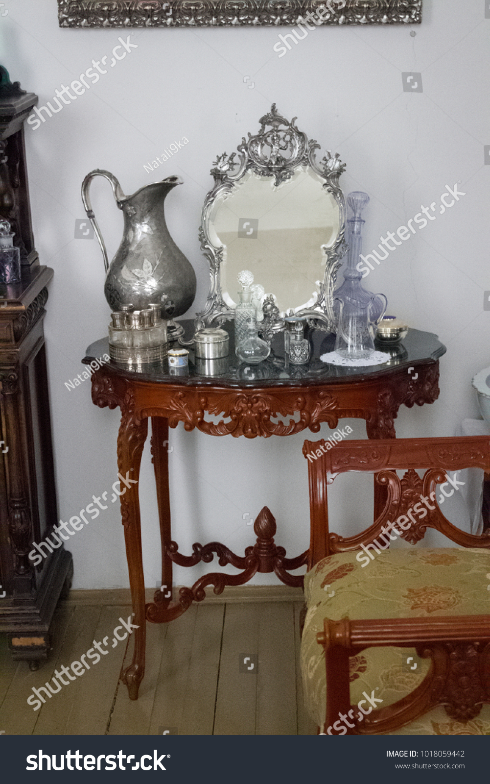 Antique antique ware and bottles of women's perfume from the 18th-19th century on an antique antique table in the interior. #1018059442