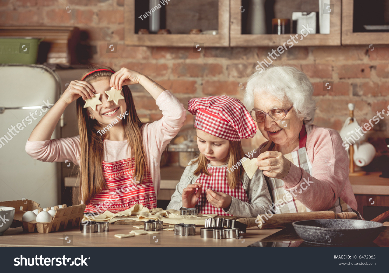Grandma teaching granddaughters to bake homemade cookies. Little girl  holding two star-shaped cookies