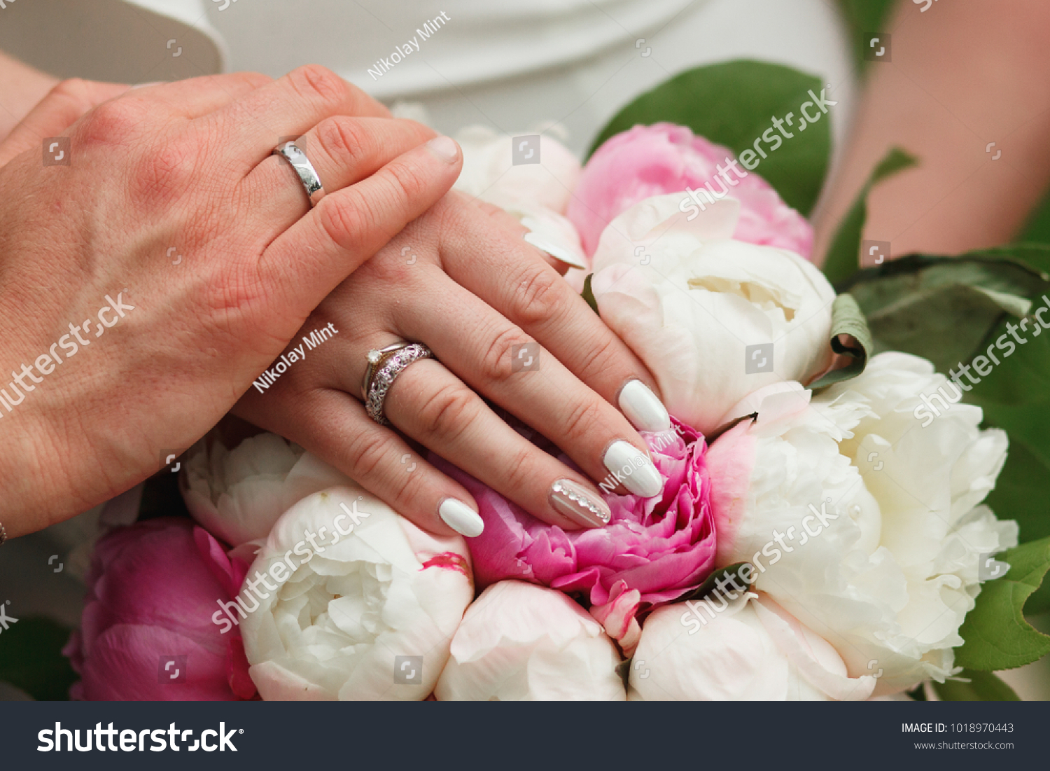 Couples hands wearing their wedding rings resting on the wedding bouqet #1018970443