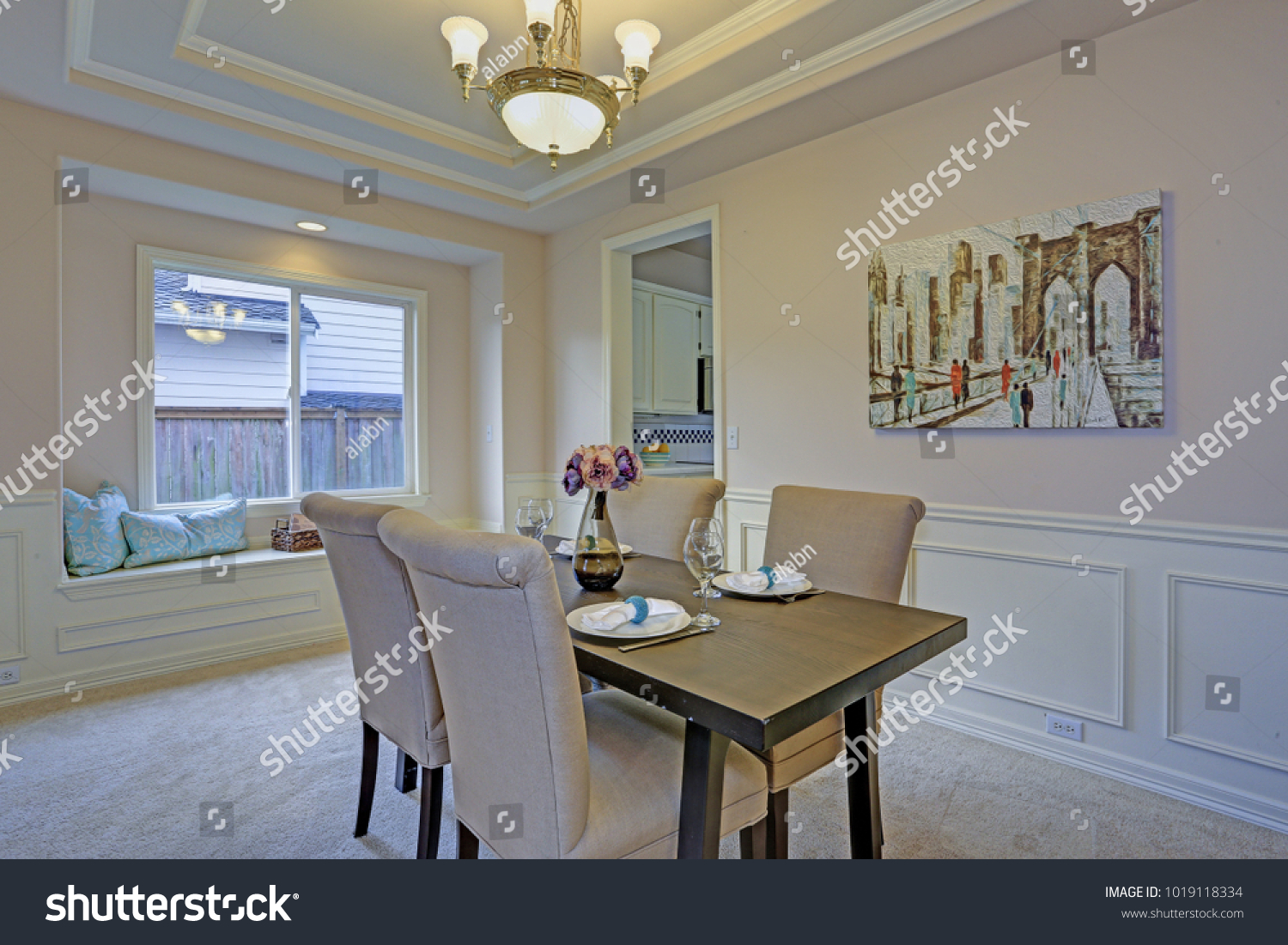 Chic Dining Room With Light Grey Walls Accented With Wall Panel Mouldings  Under Tray Ceiling.