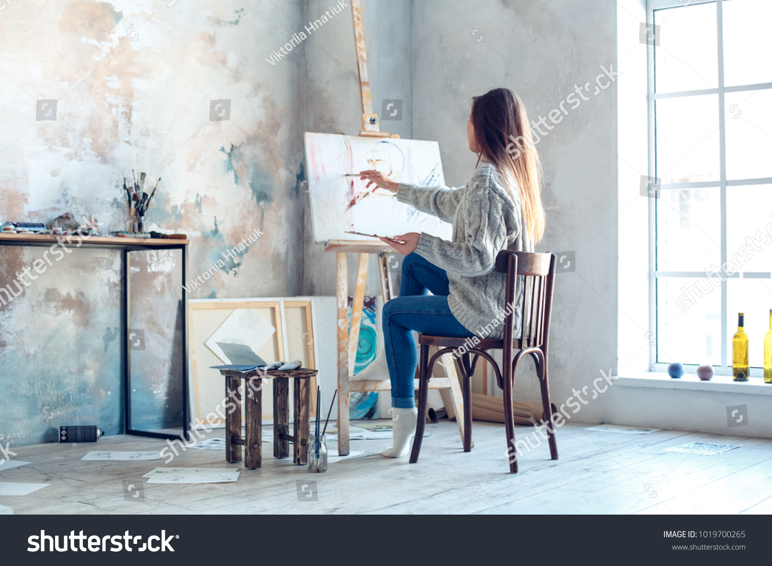 Young woman artist painting at home creative painting back view #1019700265
