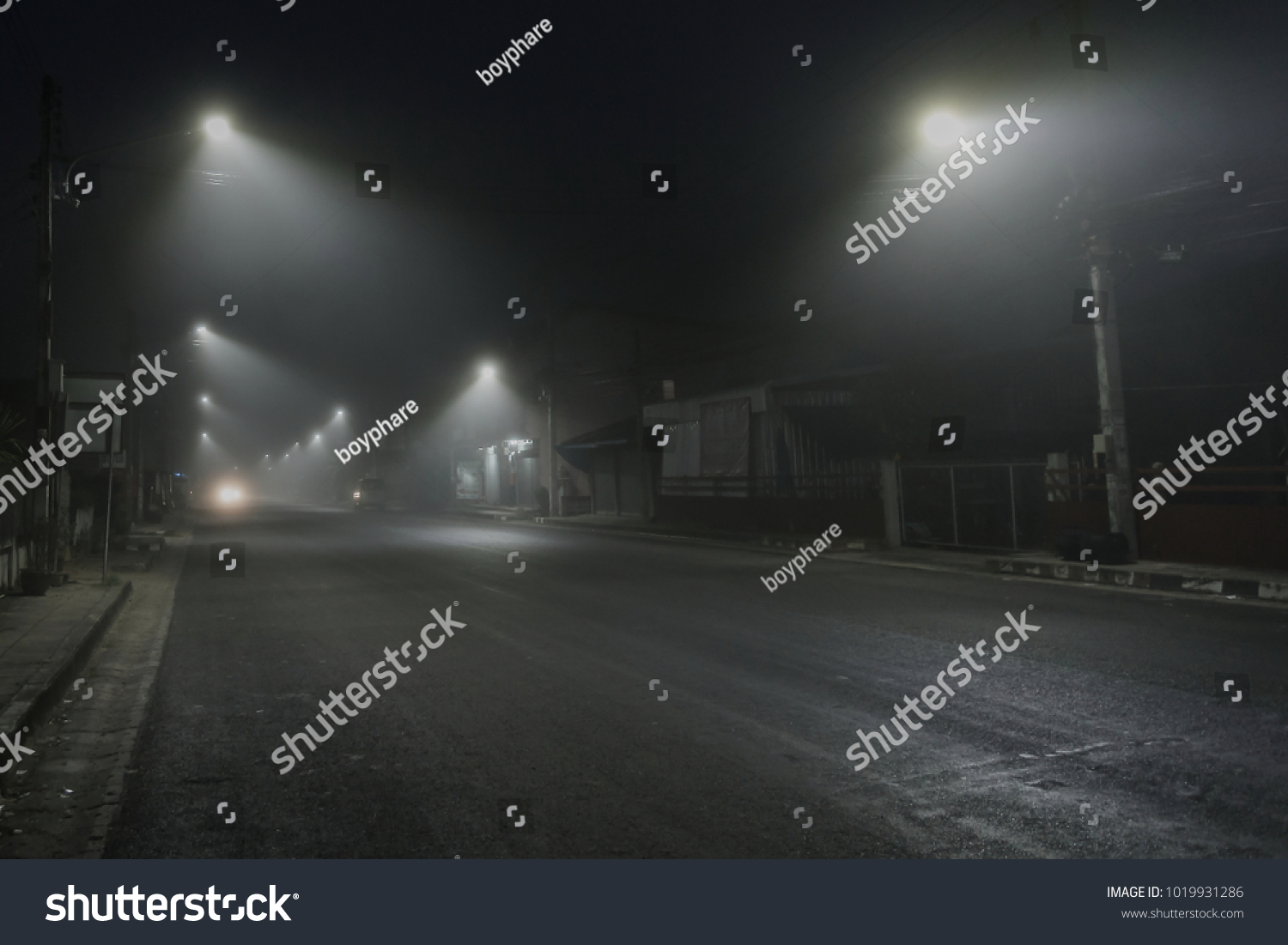 street Morning mist Street lights foggy misty night lamp Alley at the foggy street at night blur. #1019931286