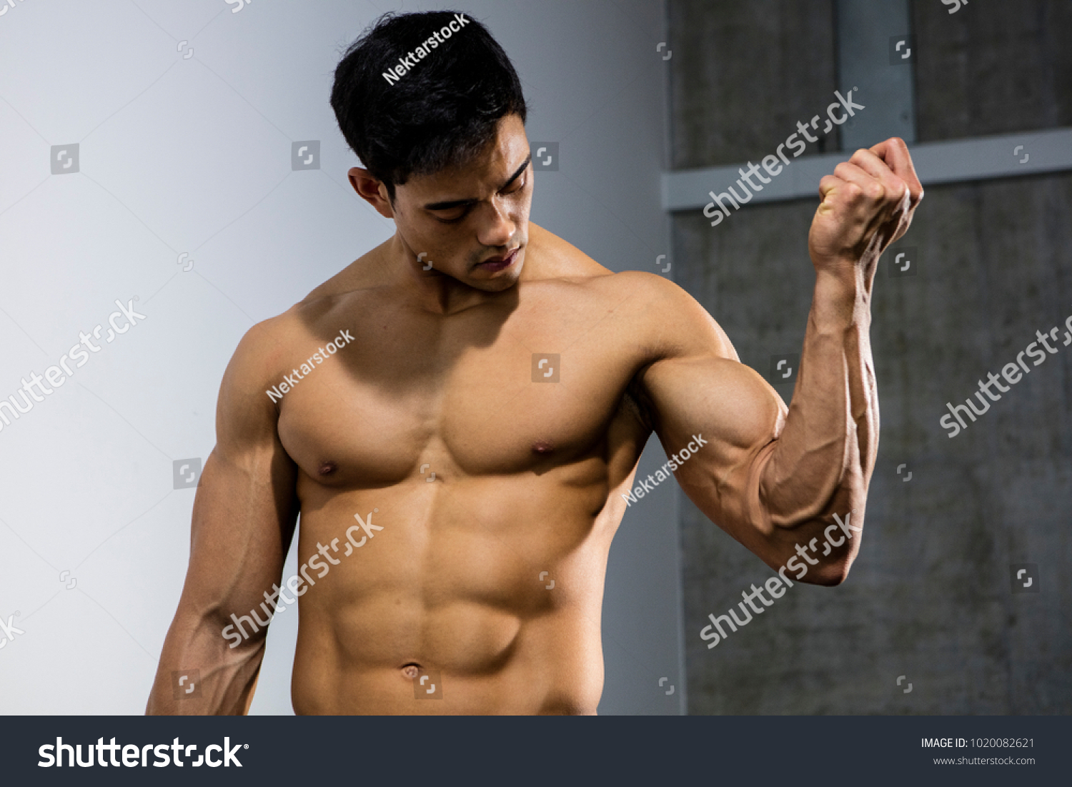 Asian Fitness Model Flexing His Bicep Stock Photo Edit Now
