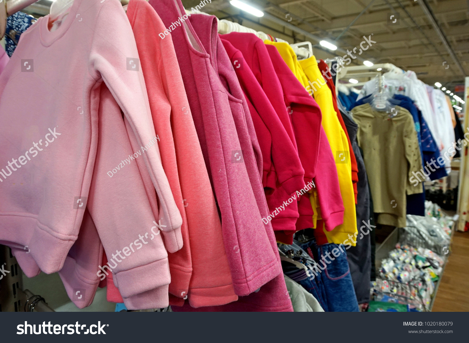 Warm colorful sweaters hang on hangers inside of a shopping mall. Beautiful  clothes for winter aeb4d0de7