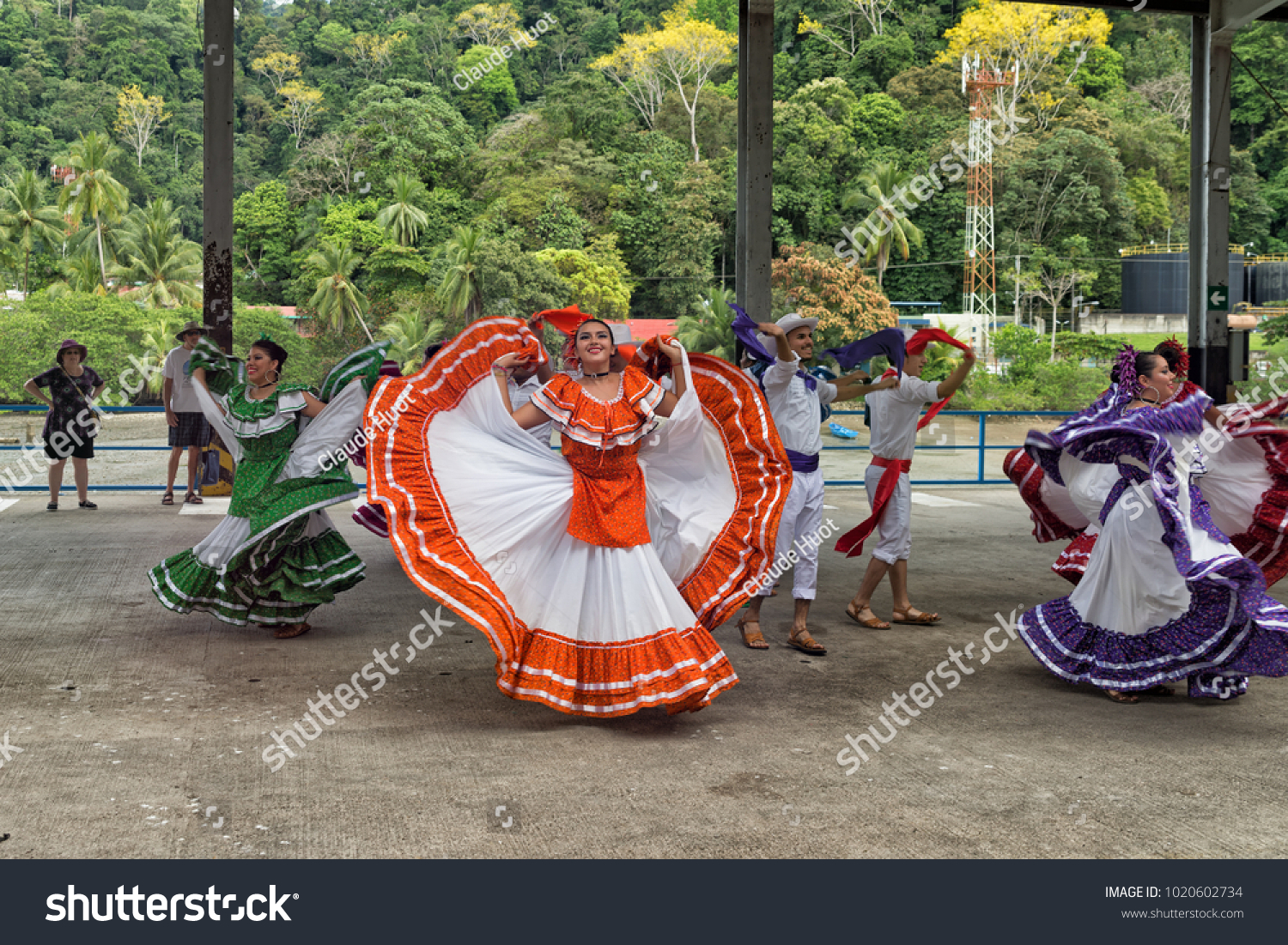 GOLFITO, COSTA RICA - JANUARY 20, 2018: Costa Rican folkloric dance troupe performs on the pier for the passengers of a cruise ship with the forest in the background.