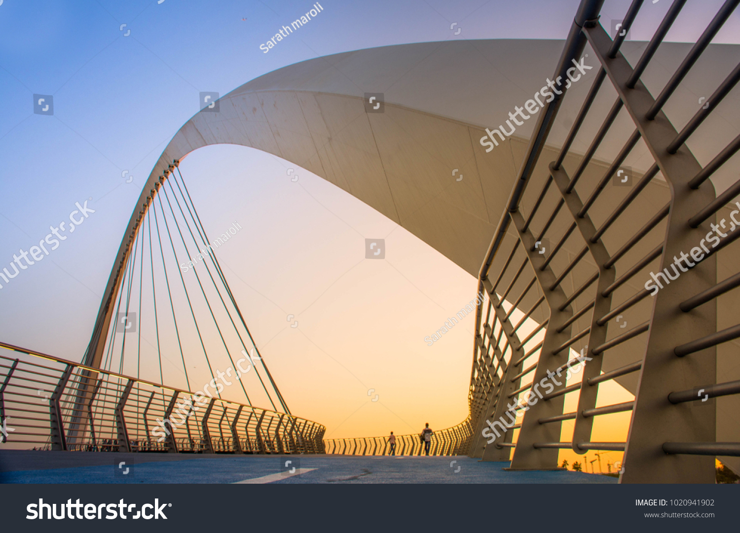 Evening shot of Dubai FamousWater Canal Bridge New Attraction of Dubai City, place to visit in UAE, tourist place in Dubai, travel destination, modern architecture beautiful sunset at Tolerance Bridge #1020941902