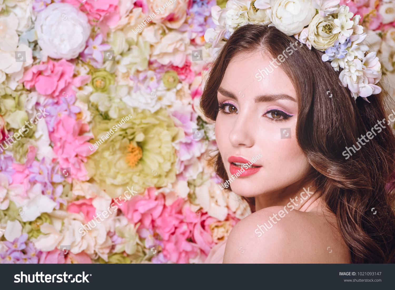 Beautiful girl with flowers wreath on head near wall from flowers id 1021093147 izmirmasajfo