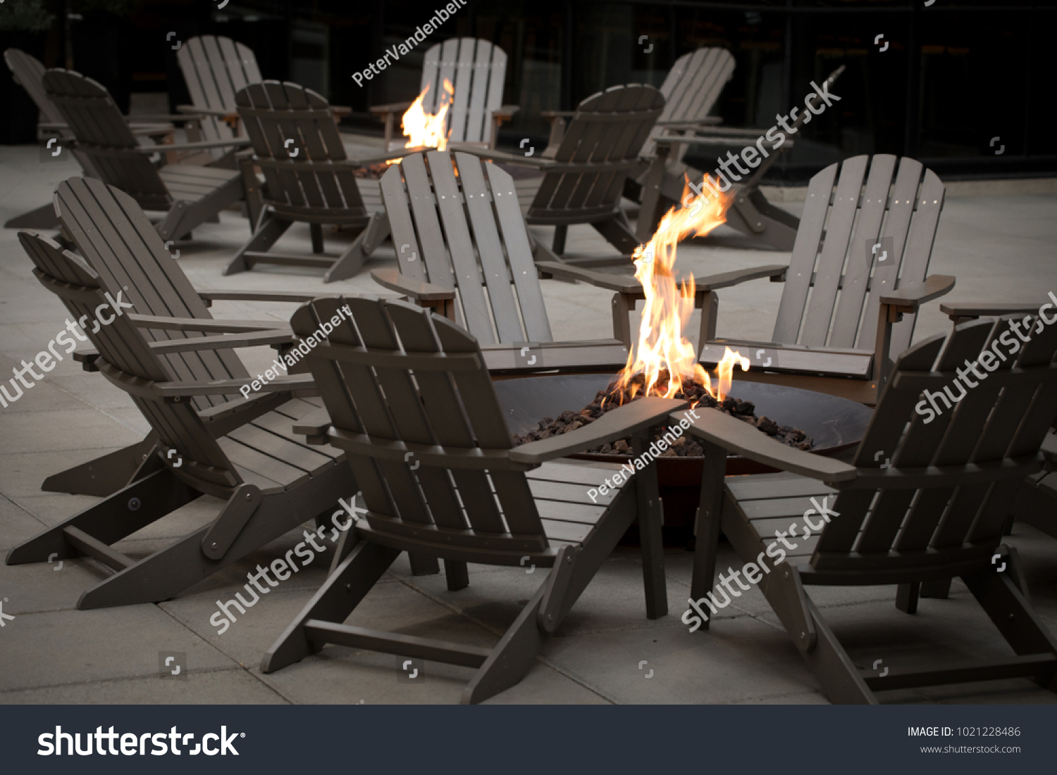 Gas Fire Pit Surrounded By A Circle Of Adirondack Chairs, With Another  Campfire In The