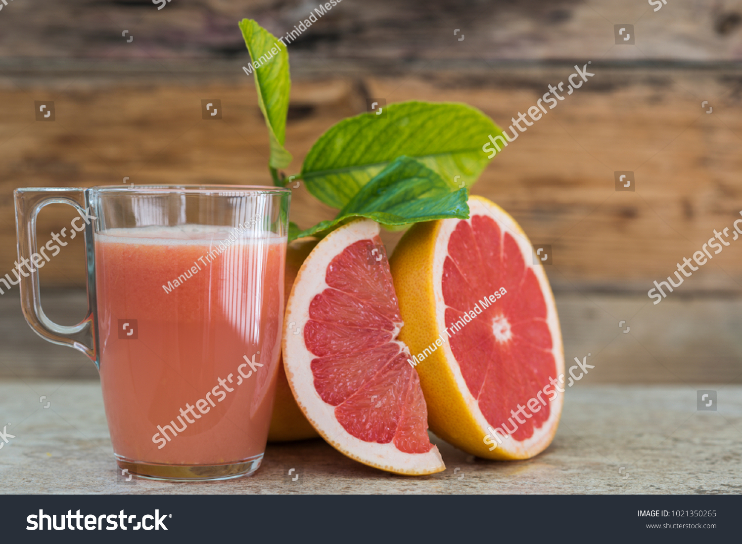 A grapefruit juice and pieces of fruit on the glass
