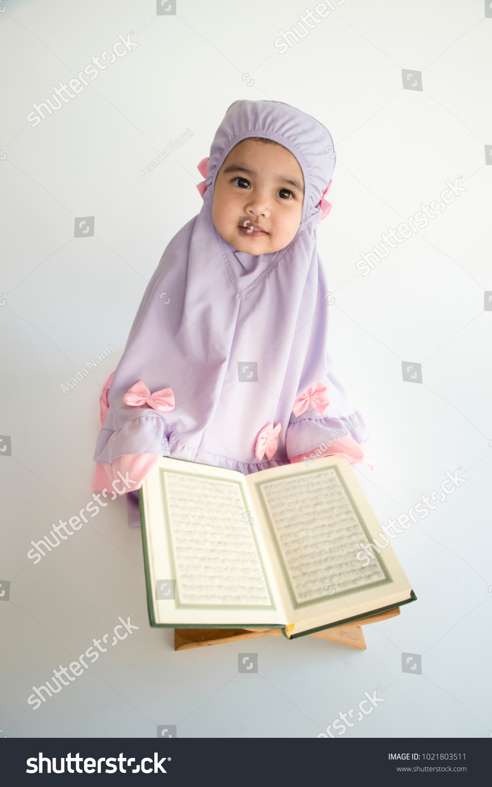Asian little cute muslim girl reading quran holy book of islam isolated on white background