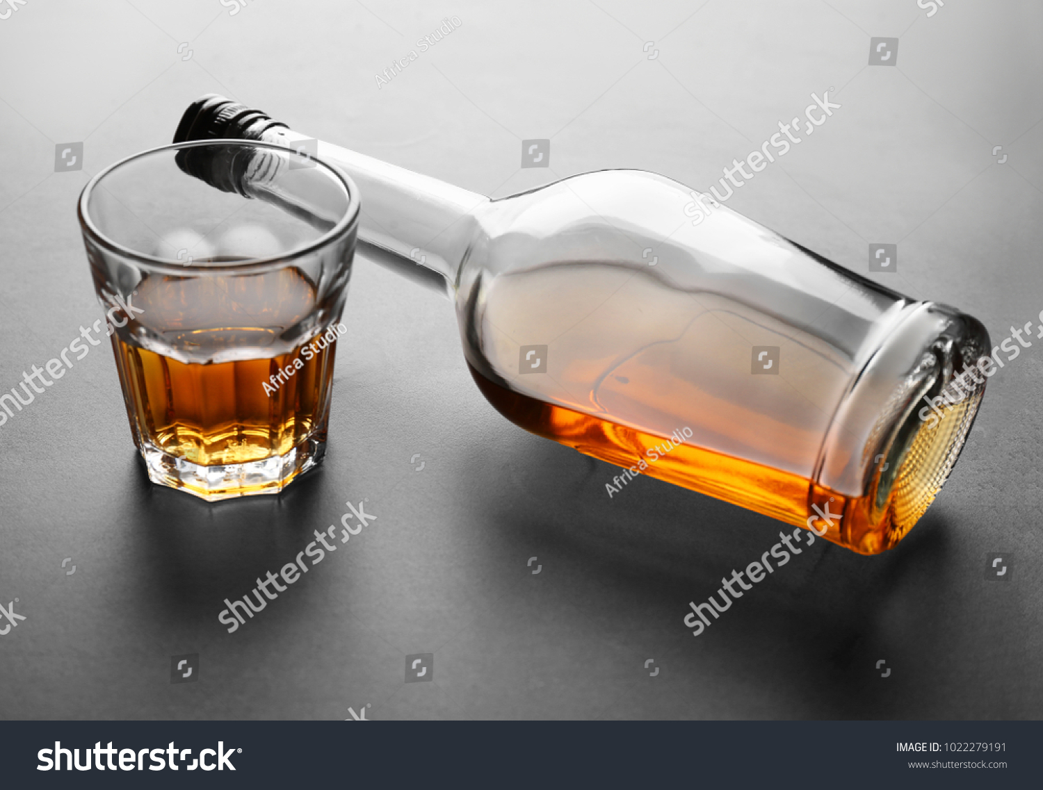 Glass and bottle of alcohol on grey background #1022279191
