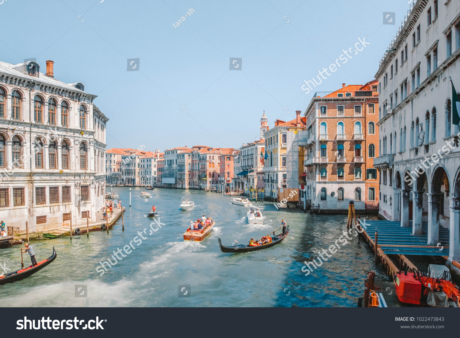 Gondolas and motor boats with tourists traveling the Grand Canal in Venice, Italy #1022473843