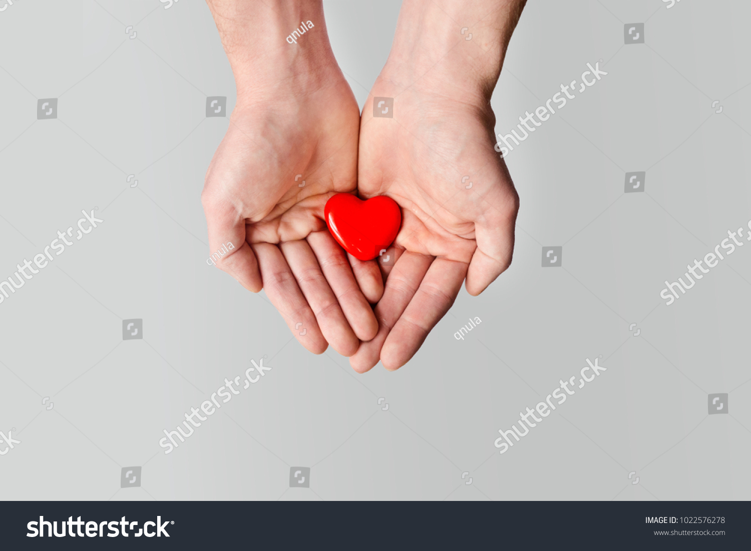 Red heart in male hands closeup on white background #1022576278