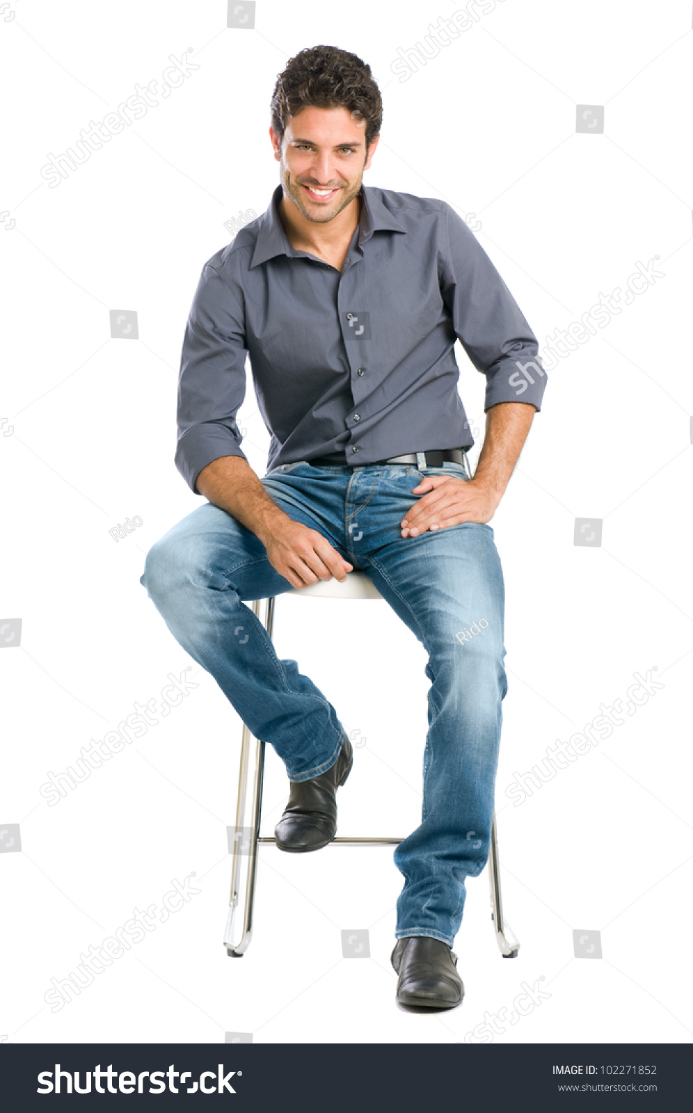 Proud And Satisfied Young Man Sitting On Chair And Looking