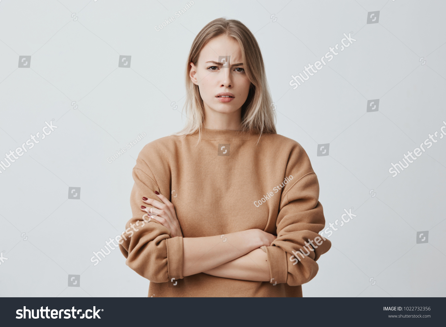 Waist-up portrait of beautiful girl with blonde straight hair frowning her face in displeasure, wearing loose long-sleeved sweater, keeping arms folded. Attractive young woman in closed posture.