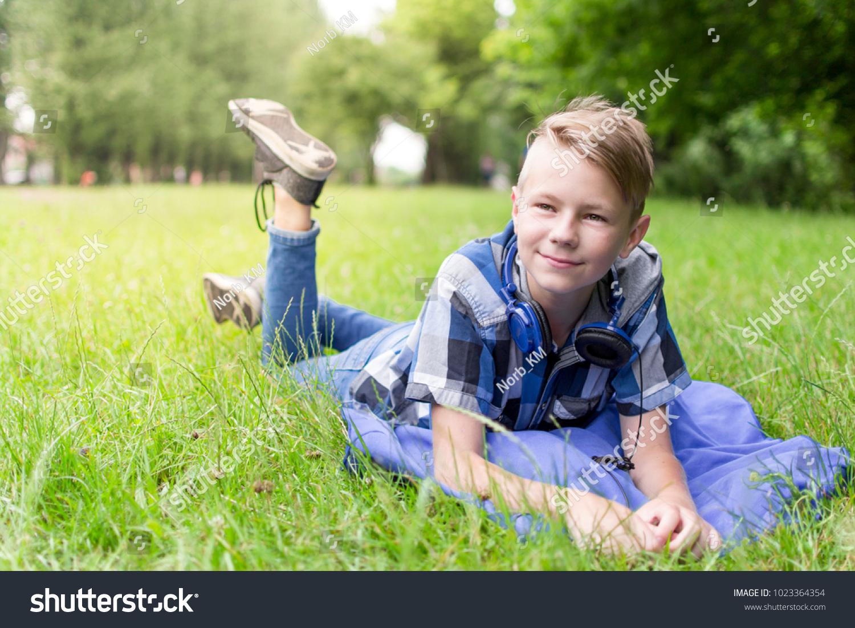 Cute little boy in blue shirt wearing headphones lying on the grass alone in summer park