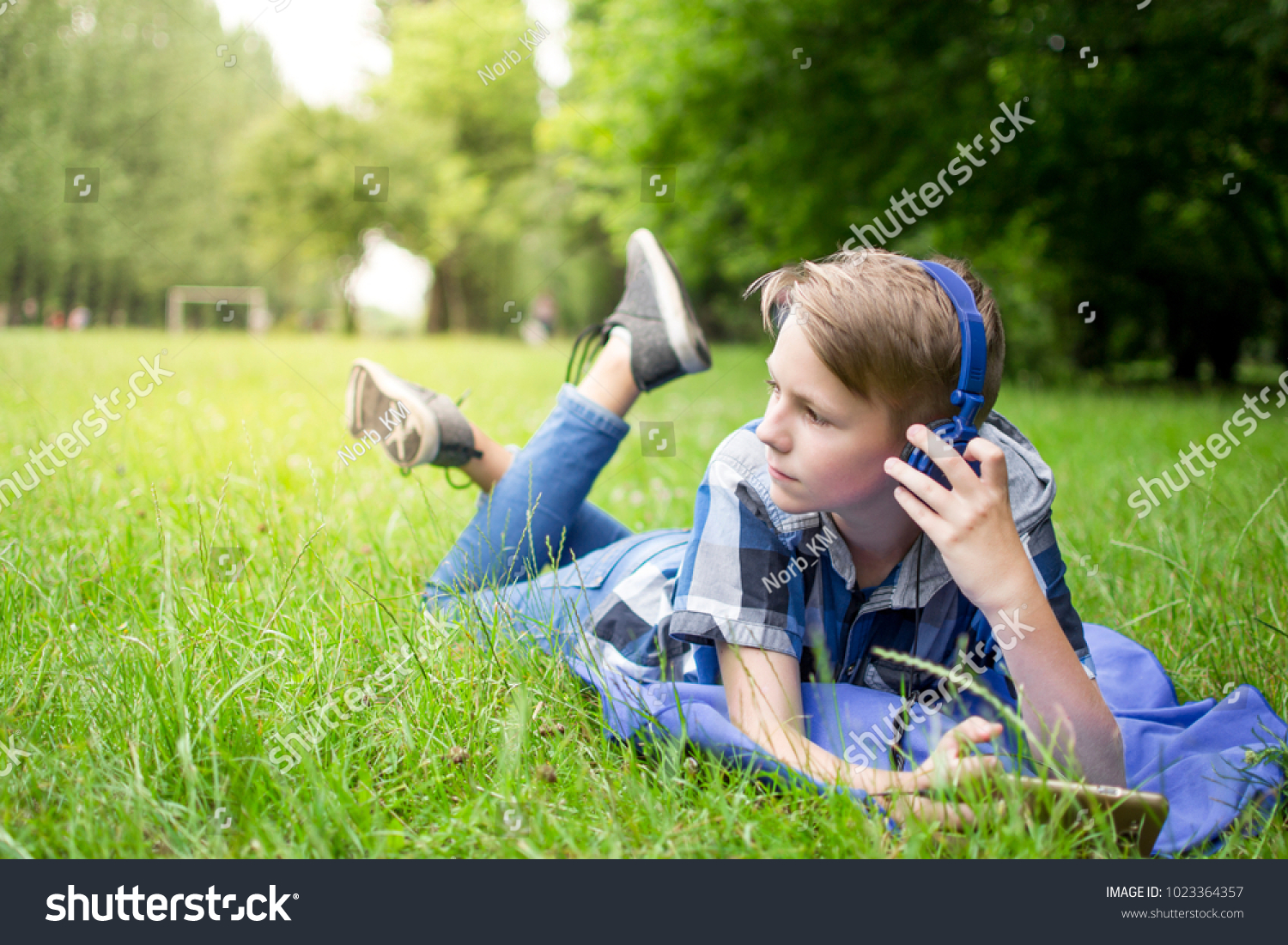Cute little boy in blue shirt wearing headphones lying on the grass alone in summer park
