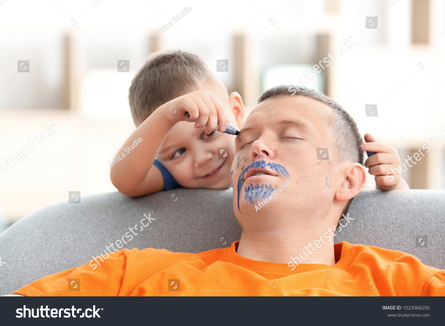 Little boy painting his father's face while he sleeping. April fool's day prank #1023966205