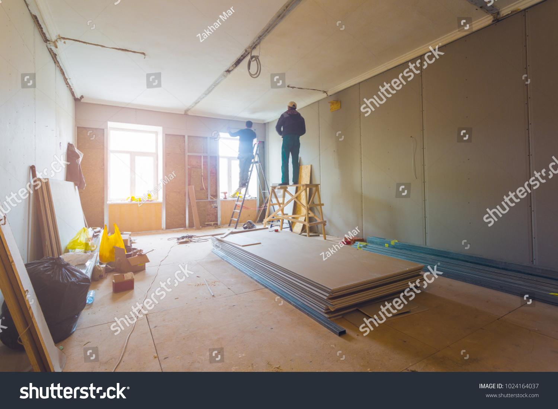 Workers Installing Plasterboard Drywall Gypsum Walls Stock