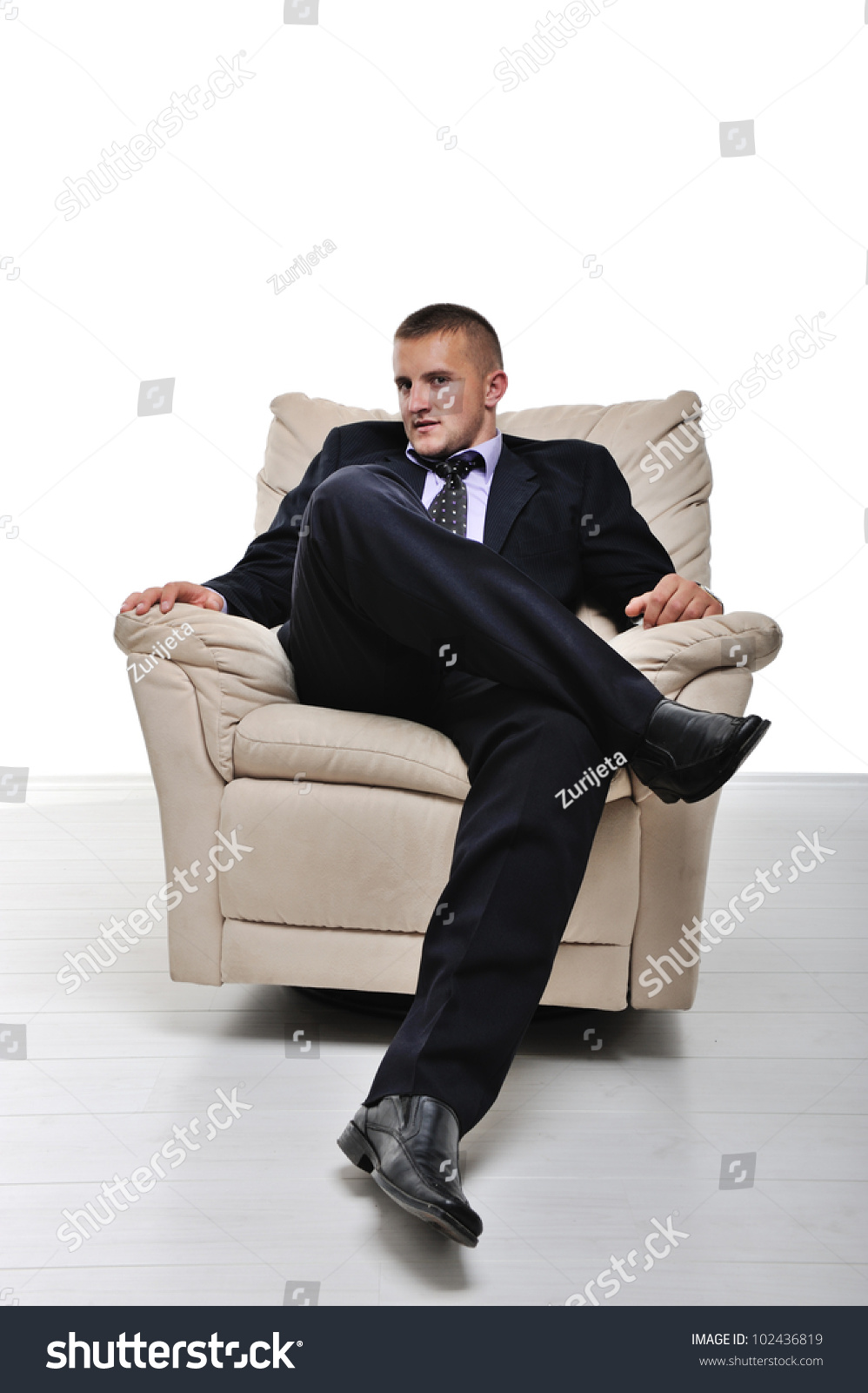 Businessman sitting armchair legs crossed isolated stock for Sitting in armchair