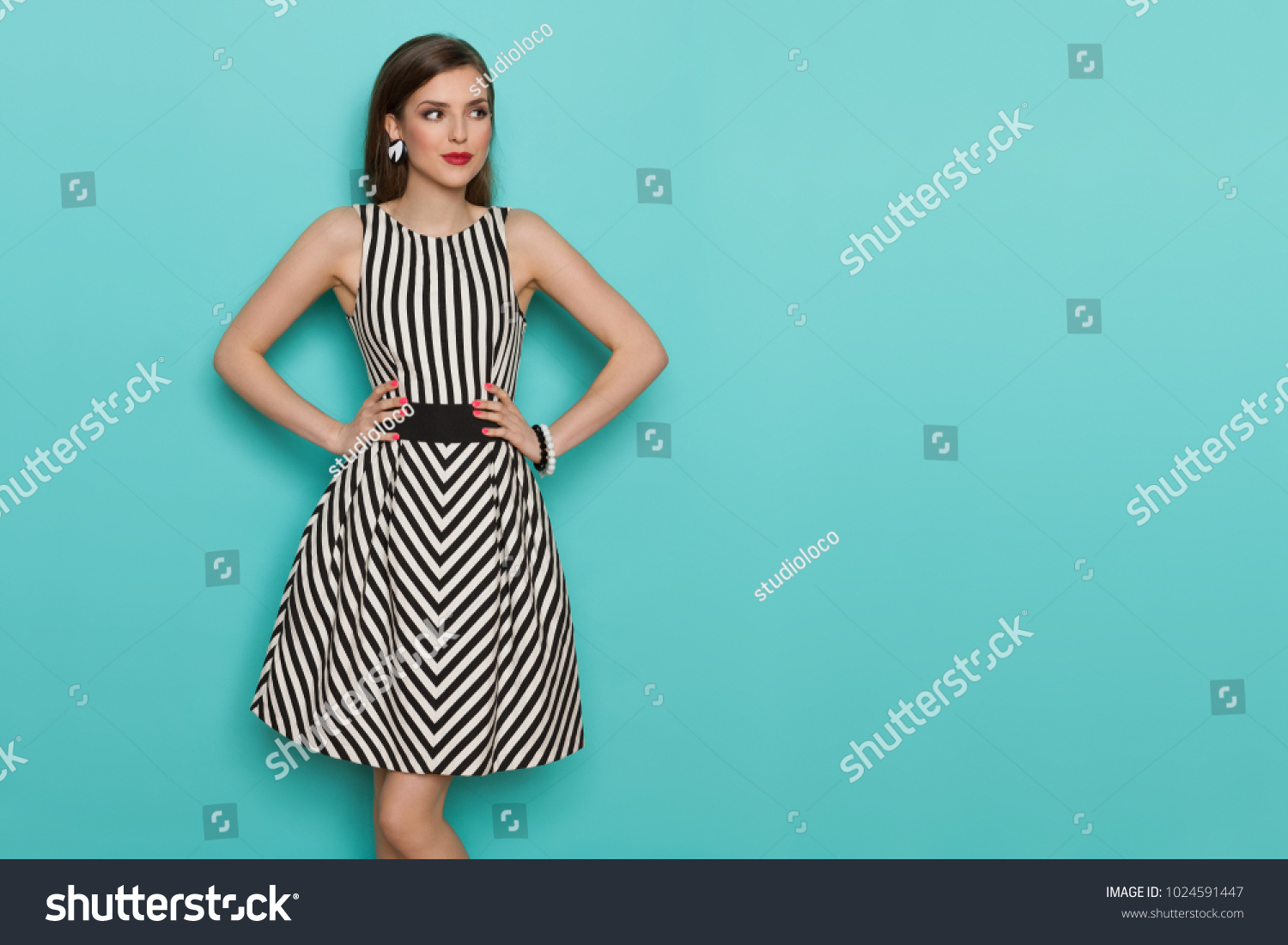 Charming fashion model in striped dress posing with hands on hip and looking away. Three quarter length studio shot on turquoise background. #1024591447