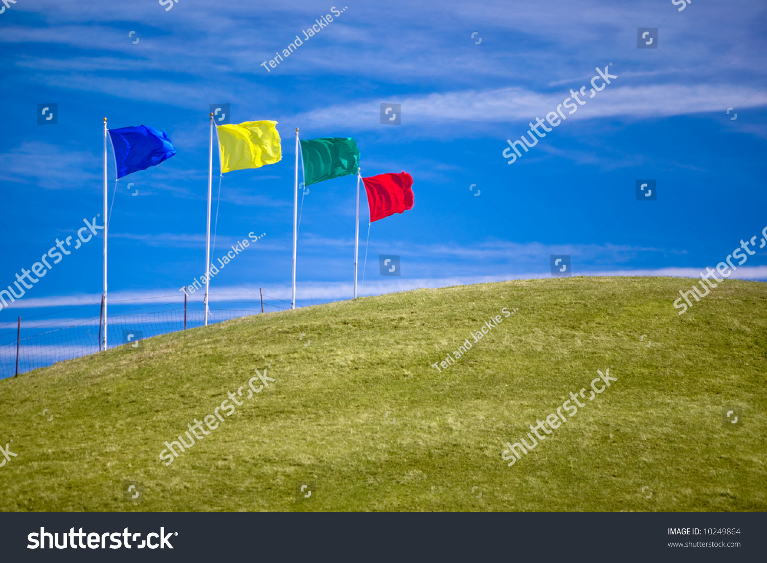 Four colorful flags on green grassy hill invite shoppers to attend an open house or other sales event.  Ample room for copy. #10249864