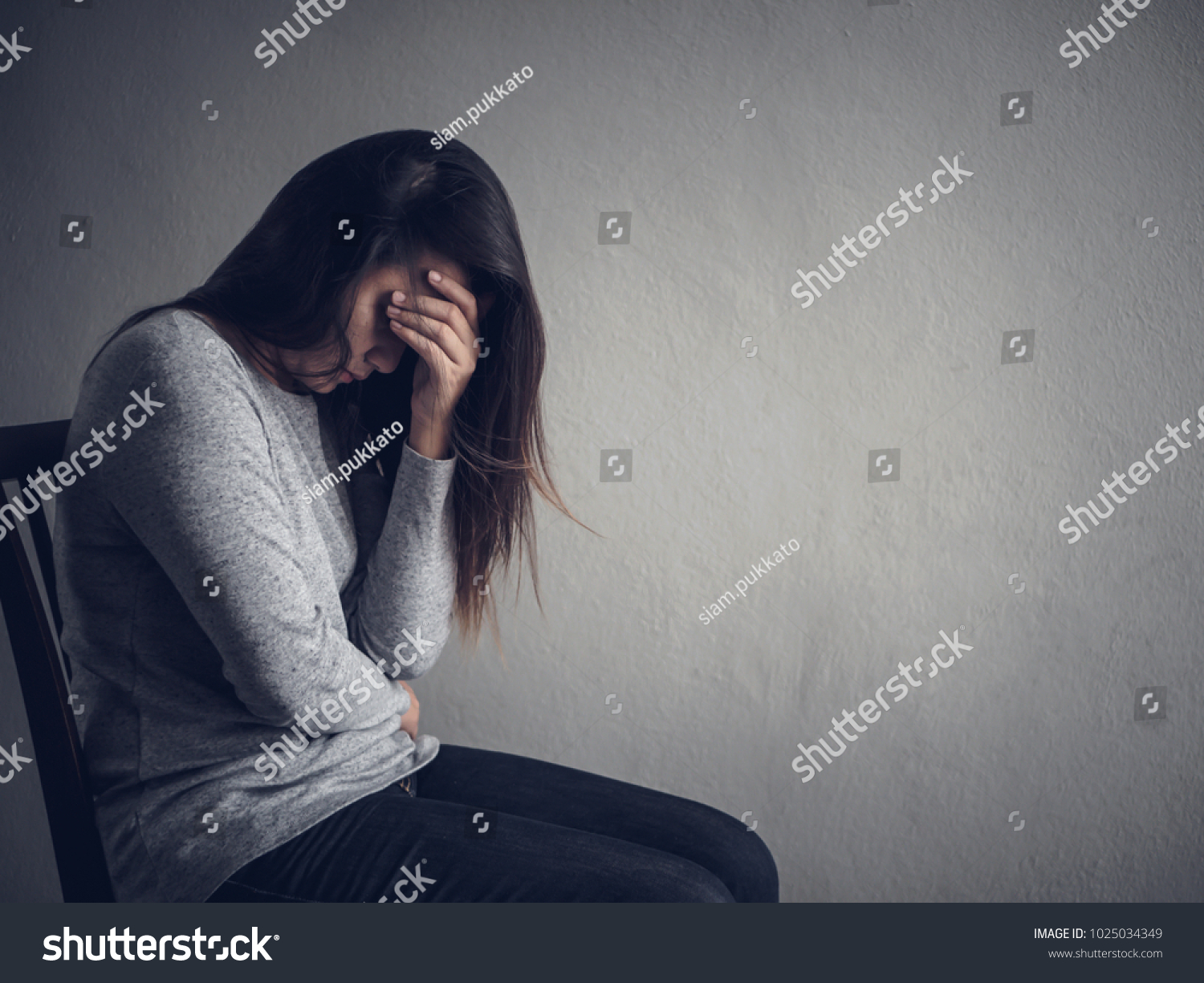 Depressed woman sitting on a chair in dark room at home lonly sad
