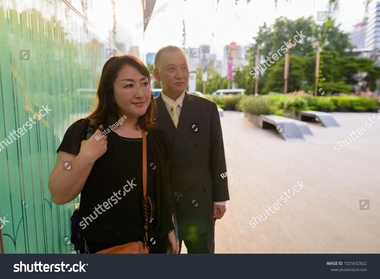 Portrait of mature Asian businessman and mature Asian woman exploring the  city of Bangkok, Thailand