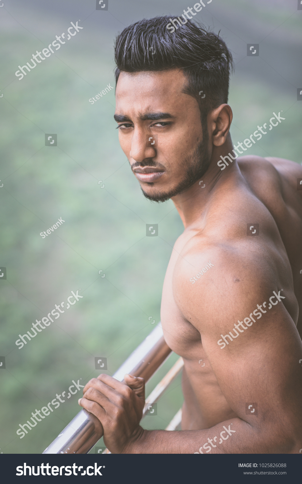 A handsome and sexy arab looking male model with fashionable thick dark  black hair and a